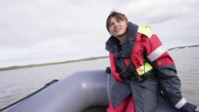 cute 10 years old boy enjoys a rubber boat trip on fjallsárlón glacier lake in iceland - boy sits in the front - 10 11 years stock videos & royalty-free footage