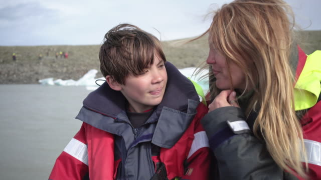 cute 10 years old boy enjoys a rubber boat trip on fjallsárlón glacier lake in iceland together with his mother - 10 11 years stock videos & royalty-free footage