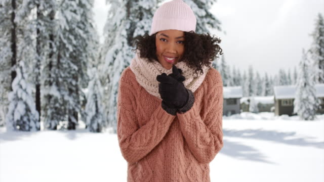 Cute African American female in cozy sweater in snowy forest, laughing joyfully