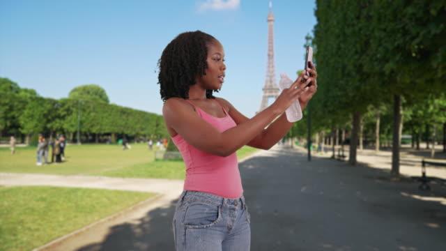 vídeos de stock e filmes b-roll de cute african american female takes selfie near eiffel tower - ensolarado