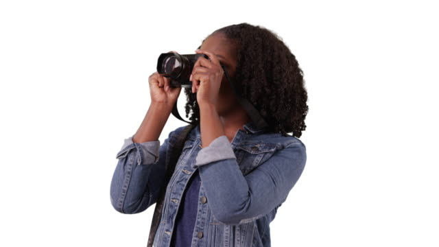 vídeos de stock, filmes e b-roll de cute african american woman looking around excitedly and taking photos in studio - jaqueta jeans