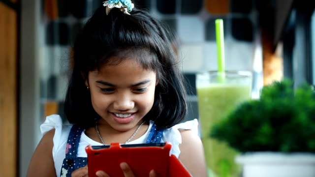 Cute African girl play tablet in coffee shop