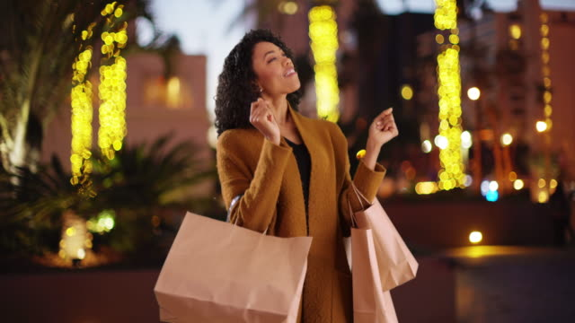 Cute African woman dancing with shopping bags in outdoor setting on lovely night