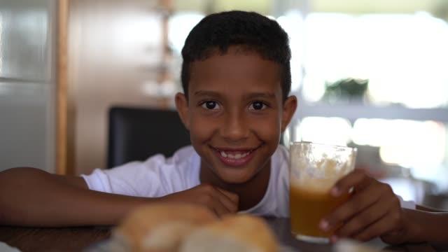 vídeos de stock e filmes b-roll de cute afro boy eating breakfast - 10 11 anos