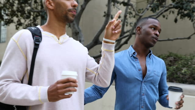 cute and affectionate gay men couple walking in the city downtown - black ethnicity stock videos & royalty-free footage