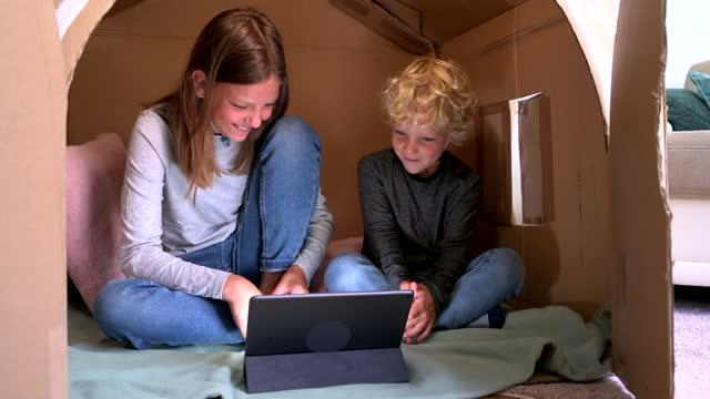 süße und glücklich kaukasische bruder und schwester sehen film auf digitalen tablet in karton haus zu hause - spielzeughaus stock-videos und b-roll-filmmaterial