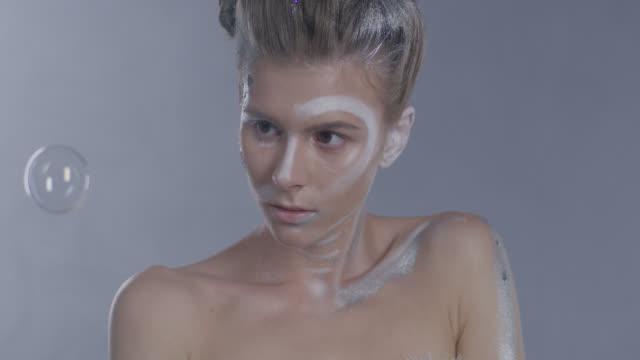 vídeos de stock, filmes e b-roll de bonito modelo de anjo, como na maquiagem de palco atrás de bolhas. vídeo de moda. - maquiagem para teatro