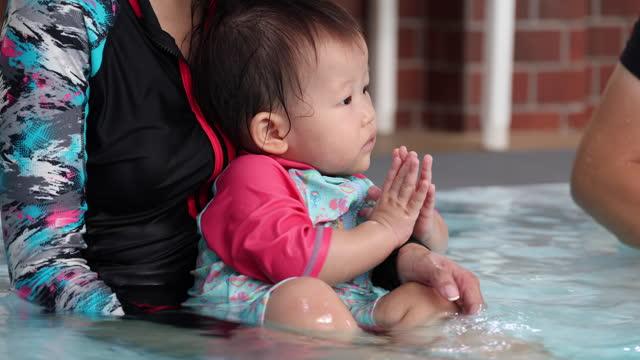 vidéos et rushes de cute asian baby at swimming pool, hands clasped, greeting with thai wai gesture - vêtement de bébé