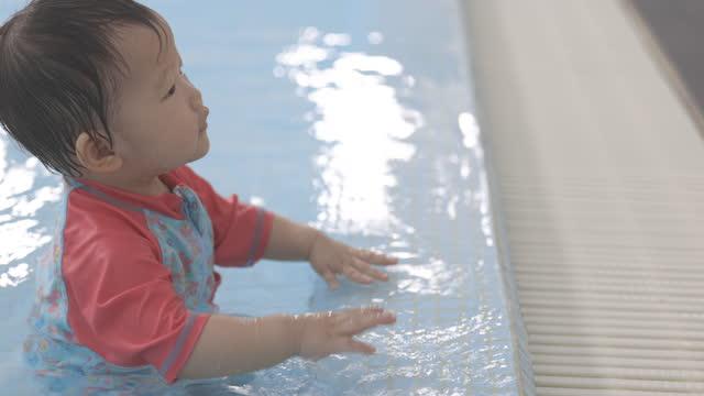 vidéos et rushes de cute asian baby at swimming pool, hold on to the edge of the pool - vêtement de bébé