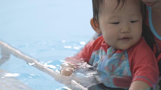 vidéos et rushes de cute asian baby at swimming pool, holding safety bar - vêtement de bébé