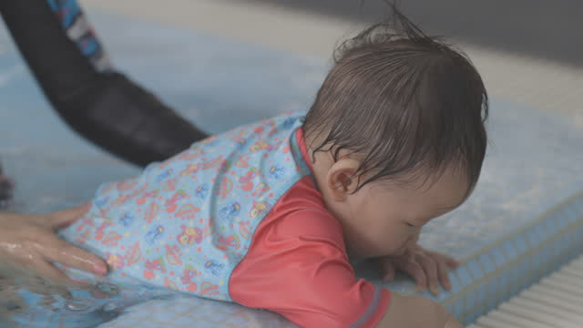 vidéos et rushes de cute asian baby at swimming pool, reaching out from the edge of the pool. - vêtement de bébé