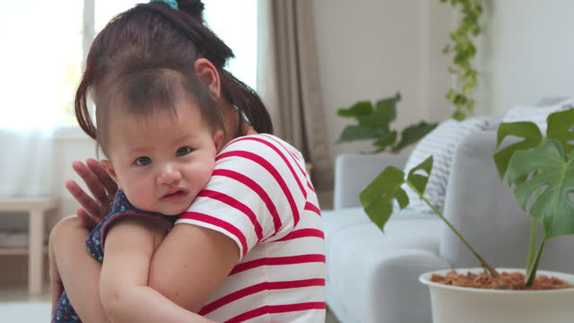 cute asian baby girl crying and her mother carrying and trying to calm and comforting with love at home in slow motion shot. childhood and family lifestyle concept. - baby girls stock videos & royalty-free footage