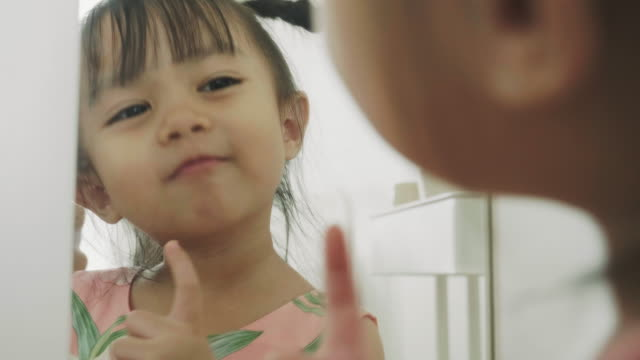 cute asian baby girl is looking at mirror - innocenza video stock e b–roll
