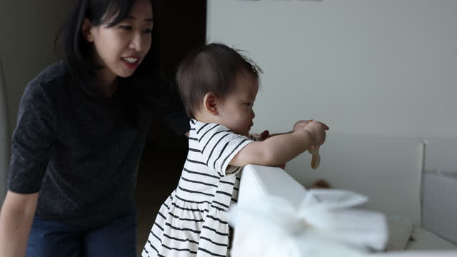 cute asian baby try to walk while holding on to her playpen edge, with mother helping near by - hair accessory stock videos & royalty-free footage