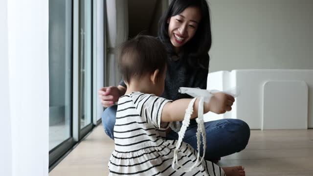 cute asian baby with mother, taking off her hair ribbon - 30多歲 個影片檔及 b 捲影像