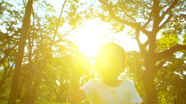 vídeos y material grabado en eventos de stock de hd : lindo niño jugando con avión de juguete asiática en el parque - avión de papel