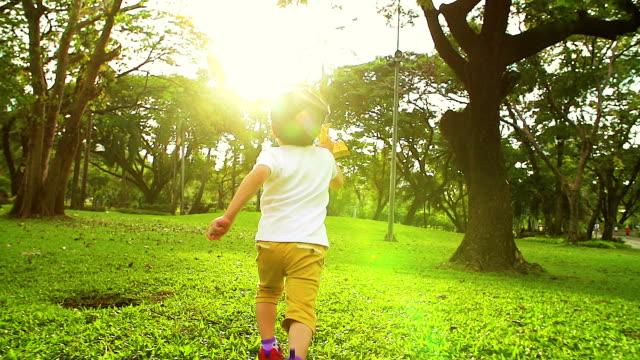 stockvideo's en b-roll-footage met leuke aziatische jongen speelgoed vliegtuig in het park spelen. - nageslacht
