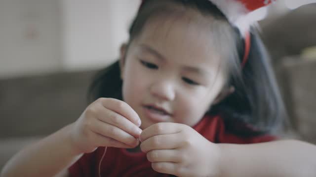 stockvideo's en b-roll-footage met leuk aziatisch kindmeisje dat parels op een koord met bedoeling en pret in huis threading. jong kind dat handgemaakte armbanden maakt om handmotiliteit te ontwikkelen. - cadeau