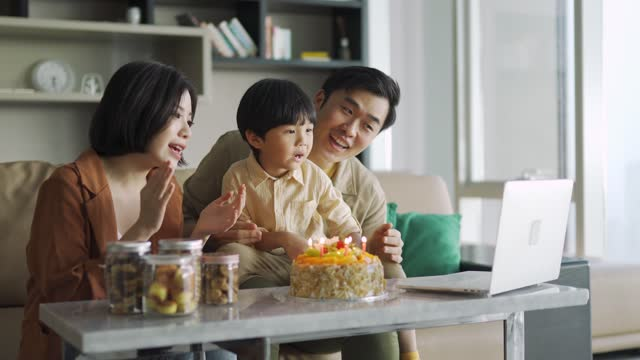cute asian chinese child celebrating his birthday cake with his parents and grandparents using online video chat - candid stock videos & royalty-free footage