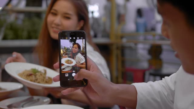cute asian couple in a cafe with smartphone - couple relationship photos stock videos & royalty-free footage