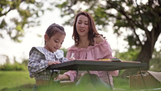 cute asian girl and mother drawing at national green park. - primary school child stock videos & royalty-free footage