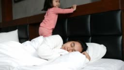 Cute Asian little girl wakes her mother up while lying on the bed at home in the morning.