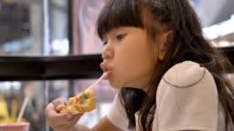 Cute asian little girls eating pizza.