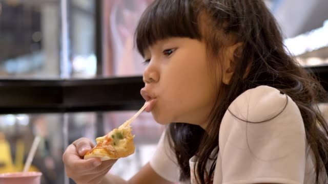 cute asian little girls eating pizza. - spuntino video stock e b–roll
