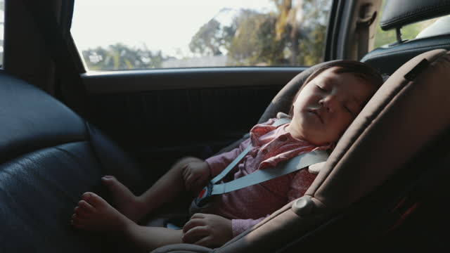 cute asian toddler girl sitting on car seat and sleeping while traveling with family. - protection stock videos & royalty-free footage