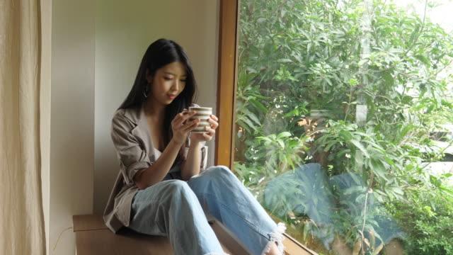 cute asian woman drink coffee beside windows - coffee drink stock videos & royalty-free footage