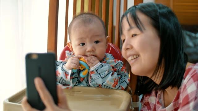söt pojke (6-11 månader) och ung mamma tar selfie med smartphone kamera skrattar - 6 11 månader bildbanksvideor och videomaterial från bakom kulisserna