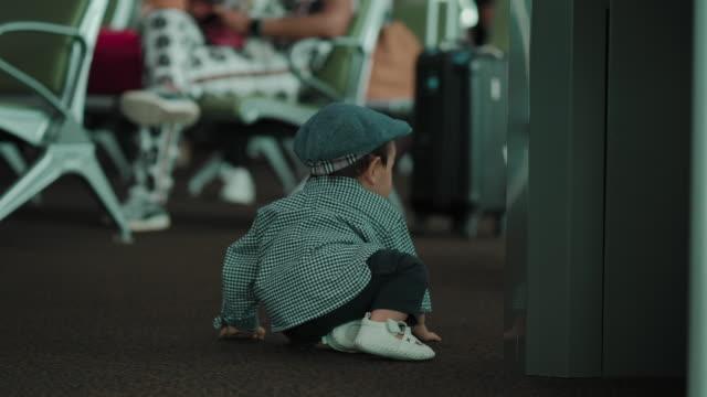 nettes baby junge kriechen auf dem boden am flughafen - 6 11 monate stock-videos und b-roll-filmmaterial