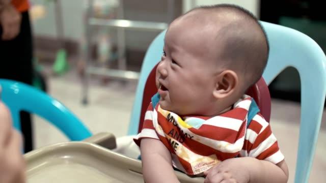 süße baby boy essen in fütterung stuhl zu hause - 6 11 months stock-videos und b-roll-filmmaterial