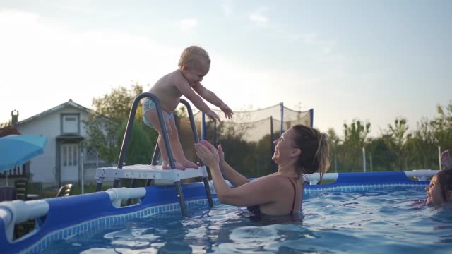 cute baby boy gaining courage to jump in the swimming pool with mother in it - one parent stock videos & royalty-free footage