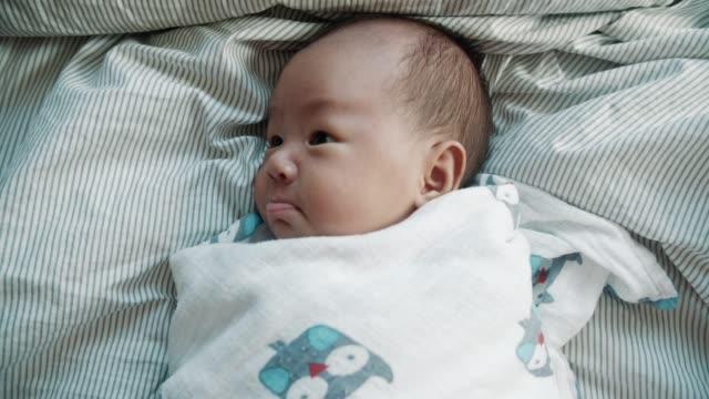 stockvideo's en b-roll-footage met schattige baby jongen in deken - pasgeborene