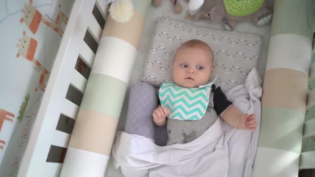 vidéos et rushes de bébé mignon dans son berceau - être étendu