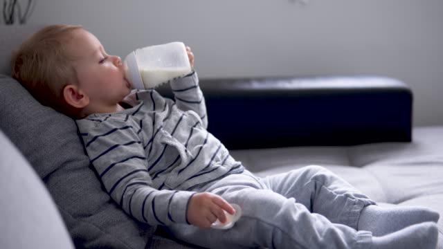 bambino carino sdraiato sul letto e beve latte - stare in piedi video stock e b–roll
