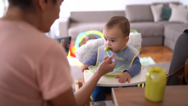 スマートフォンを見て、朝早く健康的な食べ物を食べるかわいい男の子 - feeding点の映像素材/bロール