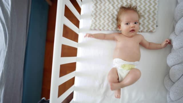 söt pojke som ligger i sin spjälsäng - endast en pojkbaby bildbanksvideor och videomaterial från bakom kulisserna