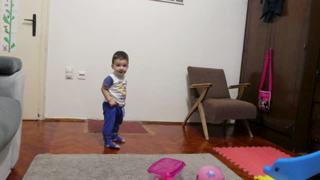 cute baby boy making his first steps and falling in apartment - carpet stock videos & royalty-free footage