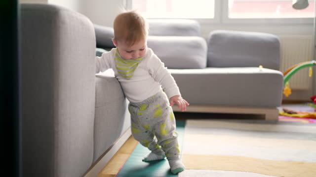 自宅で彼の最初のステップを作るかわいい男の子 - standing点の映像素材/bロール