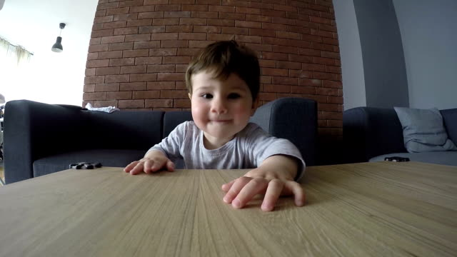 a cute baby boy trying to reach something - coffee table stock videos & royalty-free footage