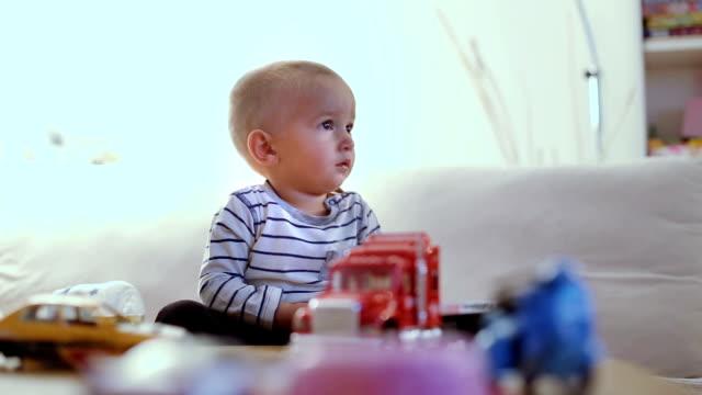 vídeos de stock e filmes b-roll de cute baby boy watching tv in living room - só um bebé menino