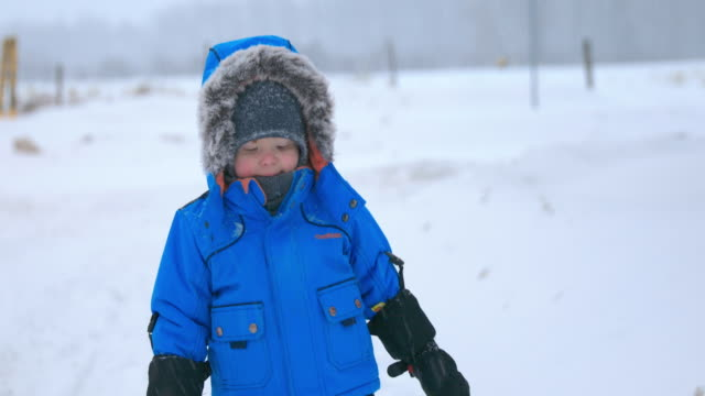 cute baby boy wearing fur coat during snowstorm - cappotto invernale video stock e b–roll