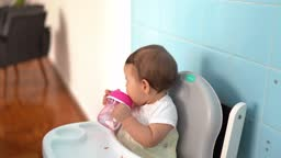 Cute baby drinking water at home