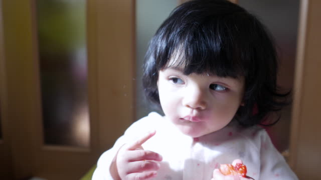 vídeos de stock e filmes b-roll de cute baby eating strawberry - vida de bebé