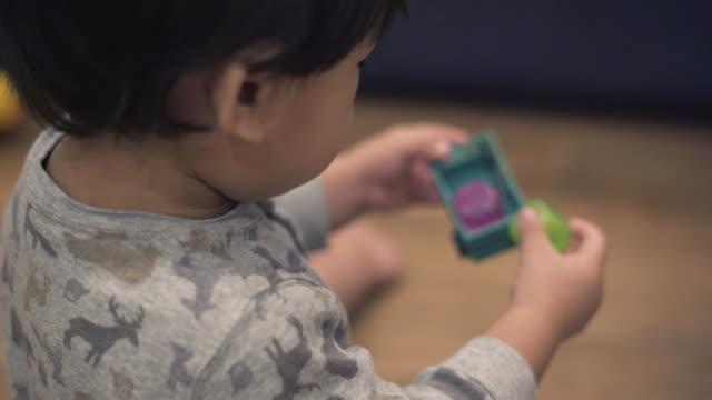 vídeos de stock, filmes e b-roll de bebê bonito divirta-se jogando o brinquedo no chão - só um bebê menino