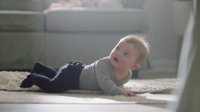 slo mo. cute baby girl crawling on carpet turns to look up and smile in sunny living room. - baby clothing stock videos & royalty-free footage