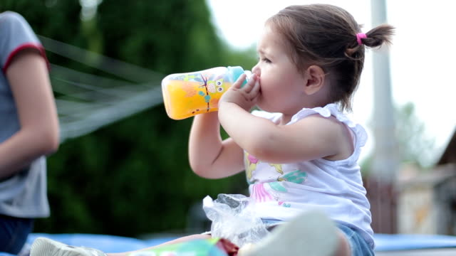 cute baby girl drinking orange juice from the bottle - orange juice stock videos & royalty-free footage