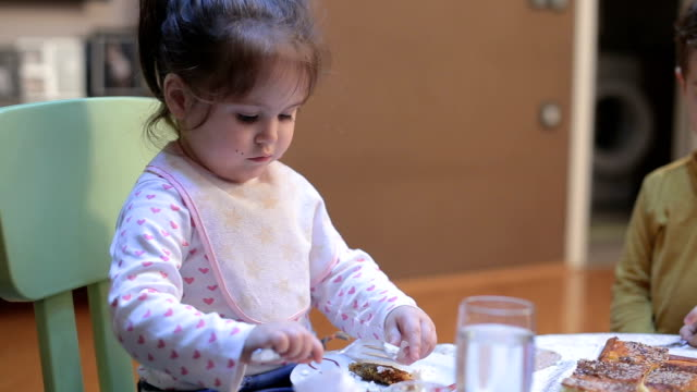 Cute baby girl eating at table with fork